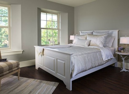 Gray Bedroom With White Bed And Dark Wood Floor